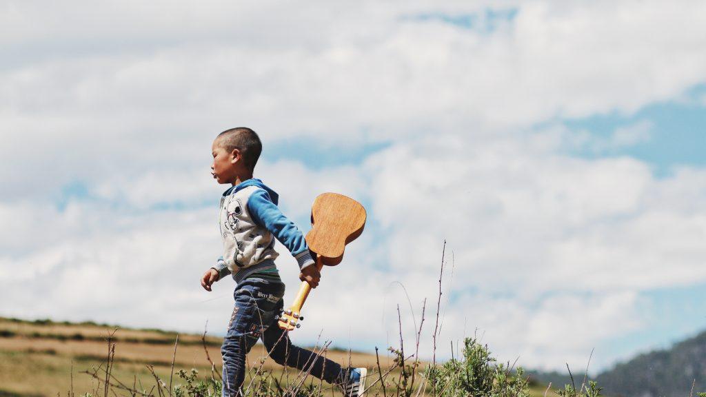 little boy running with musical instrument