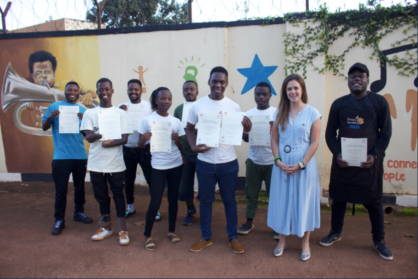 Tadeo, Sharon, Gilbert, Derrick, Victor, Steven, Micheal, Best and Allan with their ABRSM Music Exam Certificates and Director of Education, Lizzie Burrows.